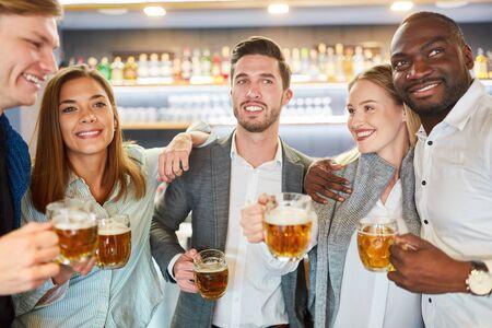 Group of friends having beer together in pub or bar after work Standard-Bild