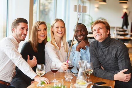 Young people as friends in the restaurant take self portrait with the selfie stick