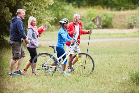 Vital group seniors doing sports together in summer in nature