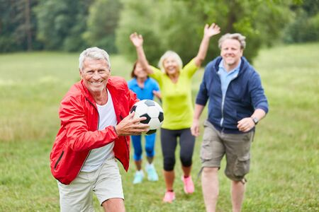 Group of seniors playing with a football at a competition or sports festival