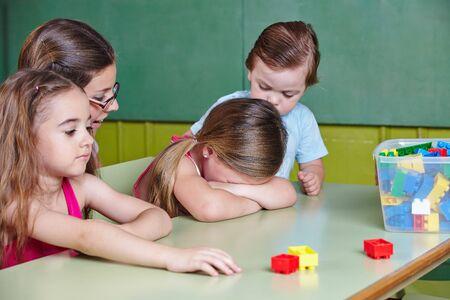 Sad child cries in kindergarten and is comforted by the kindergarten teacher Standard-Bild
