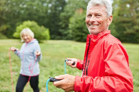 Vital senior man and partner jumping rope on a meadow in the park
