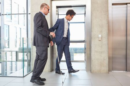 Young businessman helps a blind man with a cane at the elevator