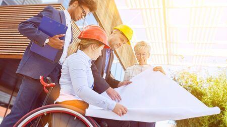 Barrierefrei bauen mit einer Frau im Rollstuhl bei der Bauplanung im Team