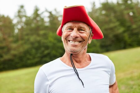 Smiling senior man at carnival or fancy dress party with red hat