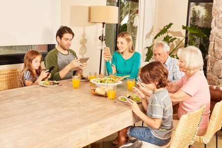 Extended family with three generations sitting at the dining table with tablet and smartphones Standard-Bild