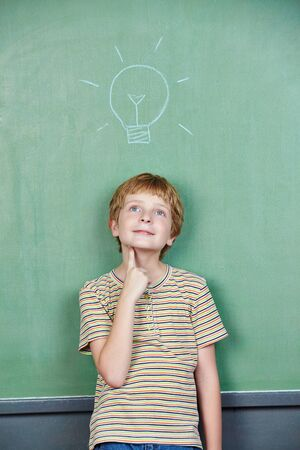 Child in front of blackboard with light bulb while thinking at school