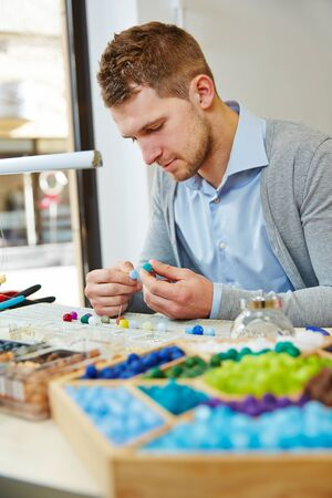Man works at the jeweler and makes a necklace