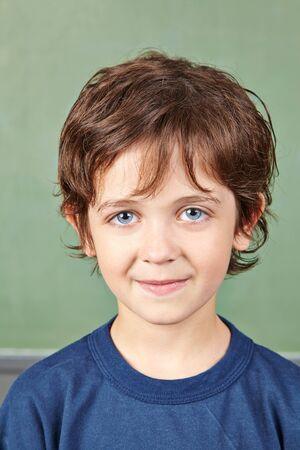 Portrait of a child in elementary school in front of the blackboard 版權商用圖片