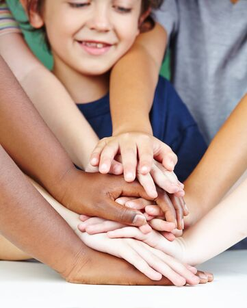 Children stack hands as a concept for collaboration and cooperation