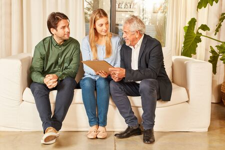 Broker with lease together with young tenant couple in new apartment