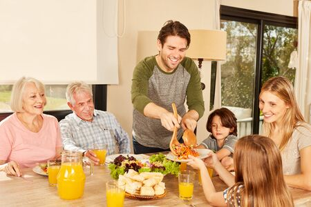 Extended family with children and grandparents having lunch at home at the table