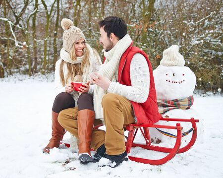 Happy couple on sledge drinks tea in winter