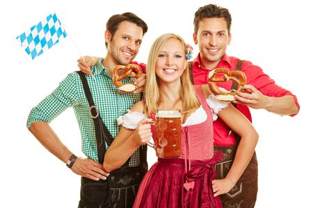 Three friends in traditional costume at the Oktoberfest with beer and pretzel