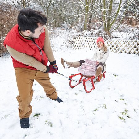 Man pulls woman with gifts on sledge in the snow at Christmas Banque d'images