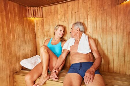 Happy senior couple in the spa sauna lovingly holds hands