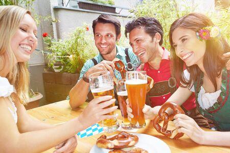 Laughing friends in beer garden in Bavaria clink glasses of beer