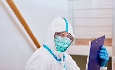 Nursing staff in nursing home in protective clothing with visitor list for coronavirus pandemic Stok Fotoğraf
