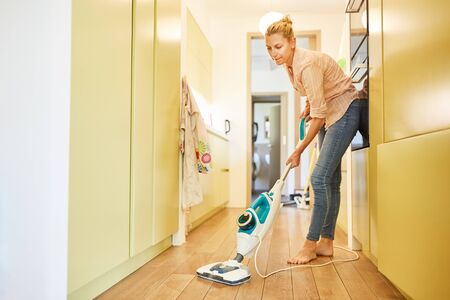 Housewife as a cleaning lady in the hallway with steam cleaner at the parquet floor cleaning