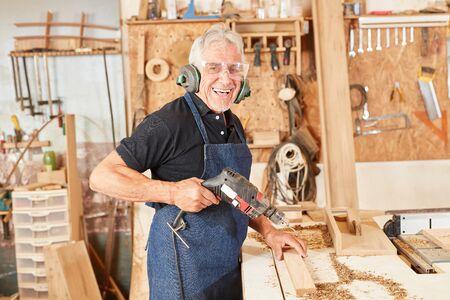 Schreiner Meister hat Spaß an der Bohrmaschine in seiner Werkstatt