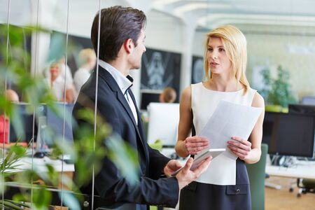 Businesswoman and businessman talk to each other about a project in the office