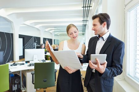 Young businesswoman with file asks a colleague for advice in the office 版權商用圖片