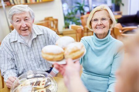 Seniors in the old people's home eat Berlin pancakes and have coffee together