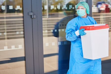 Doctor or surgeon with organ transport after organ donation for surgery in front of the clinic in protective clothing