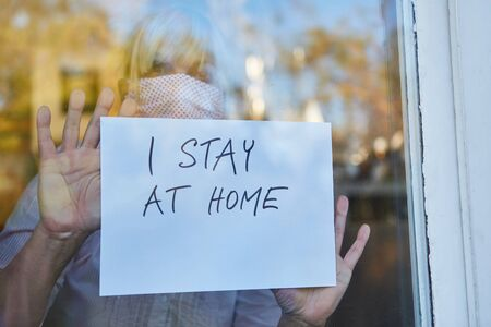 Elderly woman with a face mask holds I Stay At Home sign on the window during a coronavirus pandemic