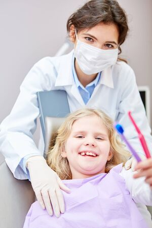 Dentist with mask and happy child with two toothbrushes for healthy dental care Foto de archivo