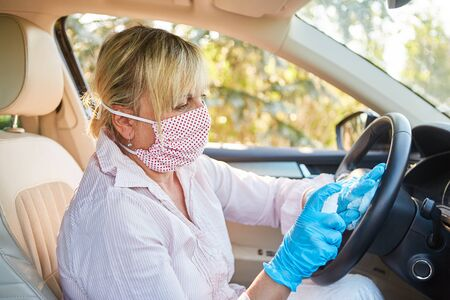Cleaner with face mask cleans and disinfects steering wheel in rental car because of coronavirus pandemic