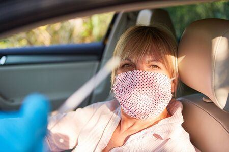 Elderly woman with face mask in her car drives in for quick test during the coronavirus pandemic