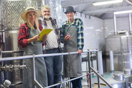 Winery team with cellar master and trainee with checklist at the fermentation tank