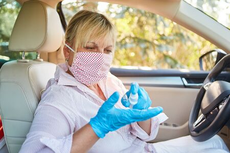 Cleaner with face mask uses disinfectants in rental cars because of coronavirus pandemic