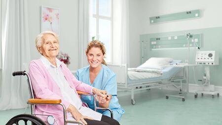 Lächelnde Seniorin im Rollstuhl mit Krankenschwester im Hospital oder Pflegeheim