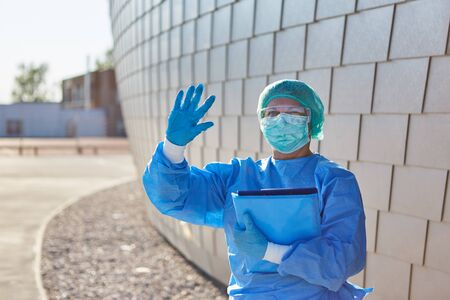 Nursing staff or containment scout with list for contact tracking gives stop signal in front of clinic during coronavirus pandemic