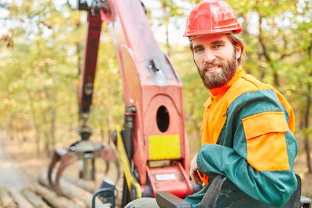 Smiling crane operator in logging on the forest crane of Forwarder in the woods