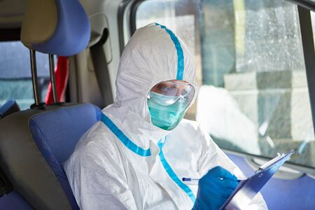 Paramedic as a containment scout is studying the contact tracking list in the ambulance during a coronavirus pandemic