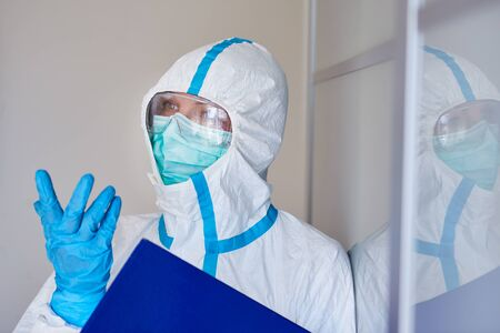 Containment Scout in protective clothing with a contact list for a suspected coronavirus case