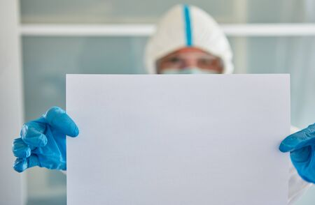 Disease control worker in protective clothing holds an empty notice board with copy space because of Covid-19 pandemic