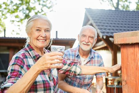 Senior couple with fresh glass of water at a fountain on a farm Archivio Fotografico