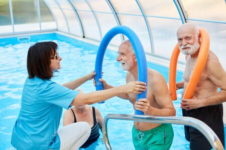 Senior and therapist together at the hydrotherapy in the swimming pool Фото со стока