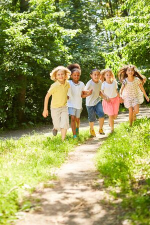 Multicultural group Children running together on a meadow Foto de archivo
