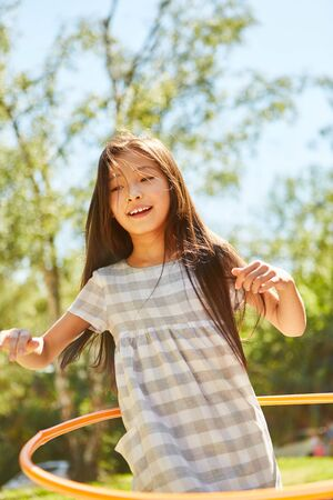 Merry asian girl in kids gymnastics with hoops in the park Фото со стока