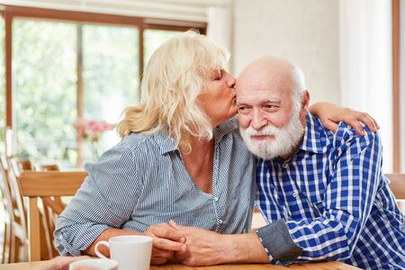 In love senior woman kisses her friend lovingly on the forehead in the retirement home