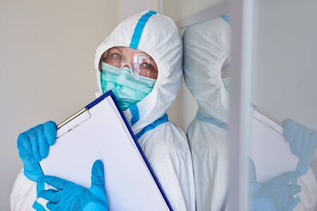 Containment scout or nursing staff in protective clothing with visitor list for contact tracking due to coronavirus pandemic
