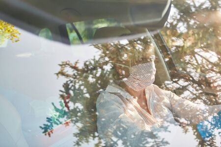 Looking through windshield at elderly woman with face mask due to coronavirus pandemic at the wheel of her car Stock Photo
