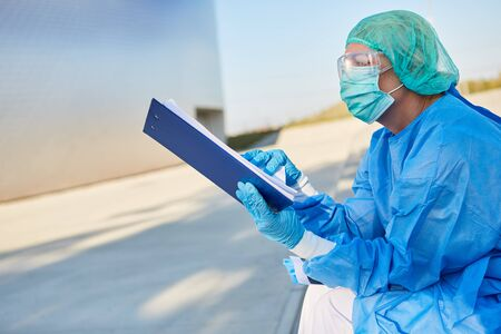 Containment Scout in front of clinic studies list for contact tracking in coronavirus or Covid-19 pandemic Stok Fotoğraf