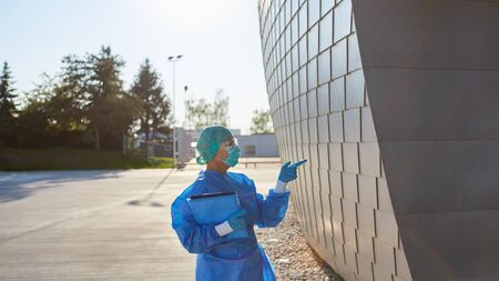 Containment scout in front of clinic makes hand signals at the entrance for admission control during coronavirus pandemic