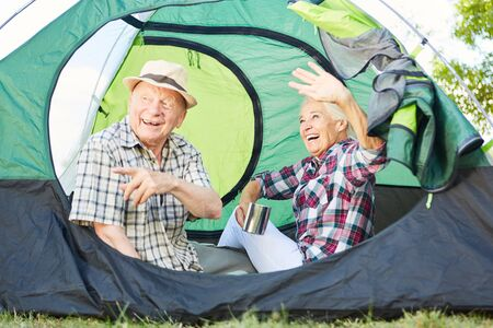 Vital couple seniors together in the tent at the campsite during summer vacation